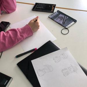 Kvinde der tegner personer med sort blyant på papir