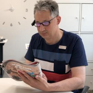 Anders læser blad ved hjælp af OrCam 2